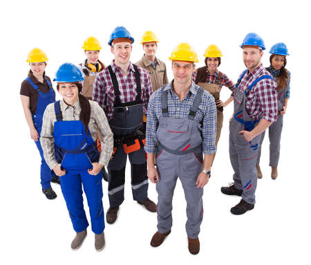 construction safety: Confident diverse team of workmen and women standing grouped in their dungarees and hardhats smiling at the camera  high angle view isolated on white Stock Photo