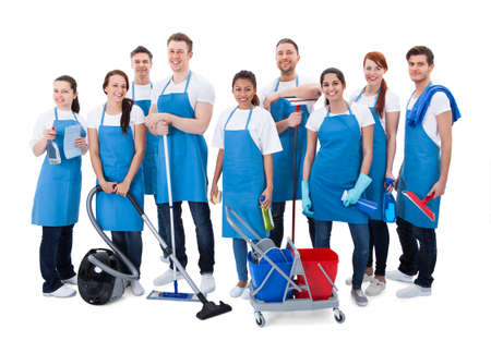 Large diverse group of janitors wearing blue aprons standing grouped together with their equipment smiling at the camera  isolated on white photo