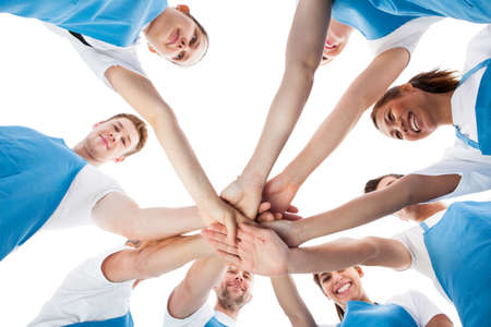 team spirit: Low angle view of cleaners stacking hands over white background Stock Photo