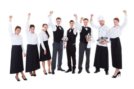 Large group of waiters and waitresses cheering. Isolated on white photo
