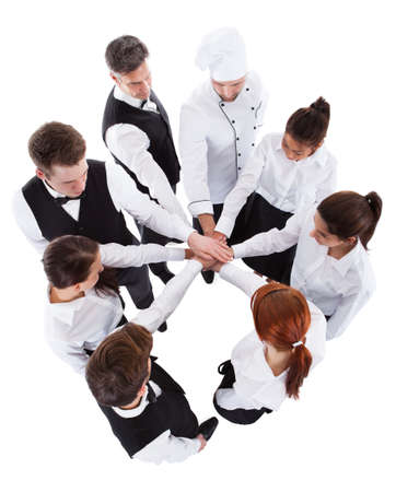 team spirit: High angle view of waiters and waitresses stacking hands. Isolated on white Stock Photo