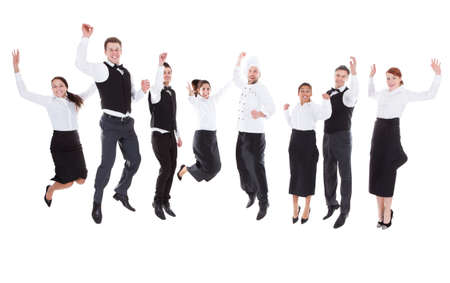 Waiters and waitresses jumping over white background photo