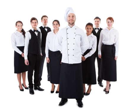 mesero: Chef de pie delante de su equipo. Aislados en blanco