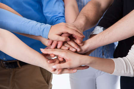 team spirit: Group of people stacking hands together. Isolated on white