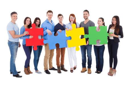 Groep mensen verbinden puzzelstukjes op een witte achtergrond Stockfoto