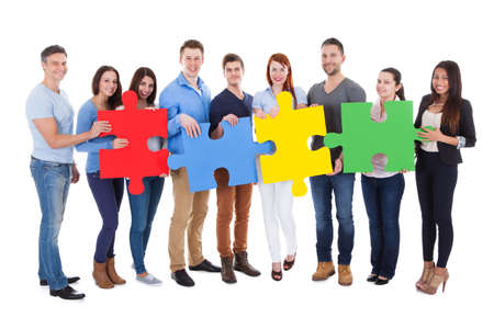 Group of people connecting puzzle pieces over white background Stock Photo