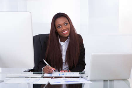 Portrait of confident businesswoman working at desk in office photo
