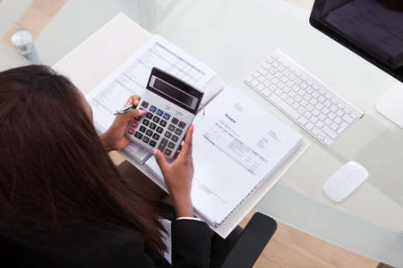 Portrait of confident businesswoman calculating tax at desk in office Stock Photo