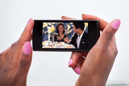 african girls: Cropped image of woman watching video on mobile phone at home