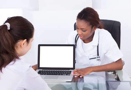 Young female dentist showing laptop patient at desk in clinic photo