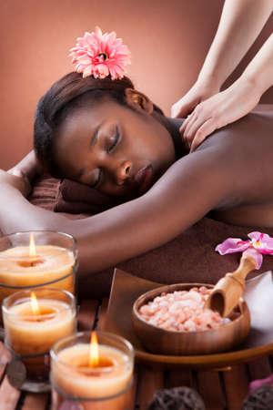 Zijaanzicht van de jonge vrouw ontvangt schouder massage in de spa salon