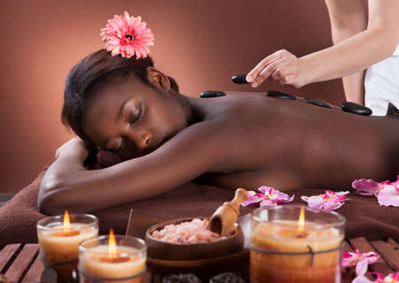Young woman getting lastone therapy at spa salon photo