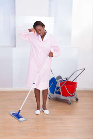 Full length of tired female housekeeper cleaning floor in hotel photo