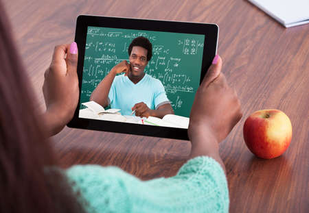 Cropped image of female teacher assisting student through video conferencing at classroom photo