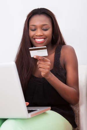 Happy African American woman holding credit card while shopping online at home photo
