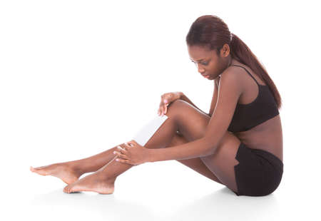 Full length of young African American woman waxing legs against white background