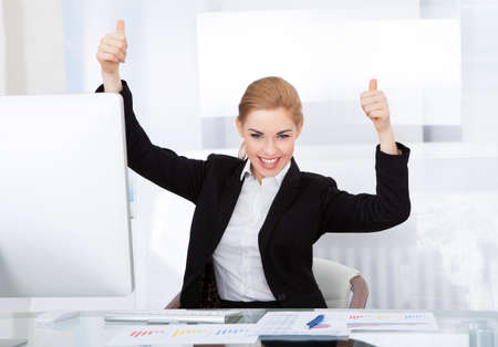 woman hands up: Happy Young Businesswoman In Office Showing Thumb Up Stock Photo