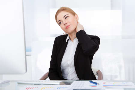 Portrait Of Young Businesswoman Suffering From Neck Pain photo