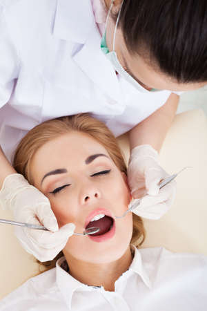 woman open mouth: High Angle View Of A Woman Having Her Dental Checkup Stock Photo