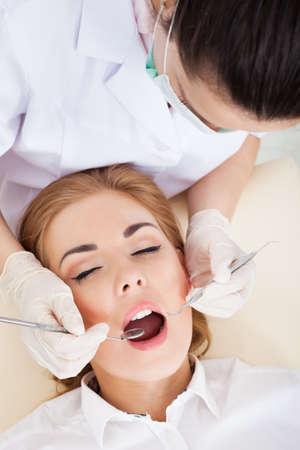 femme bouche ouverte: Vue en plongée d'une femme ayant son examen dentaire