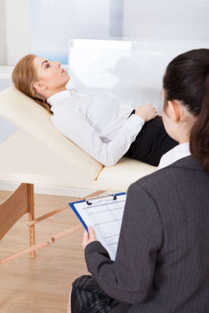 Young Female Psychiatrist Holding Clipboard Examining Businesswoman Stock Photo