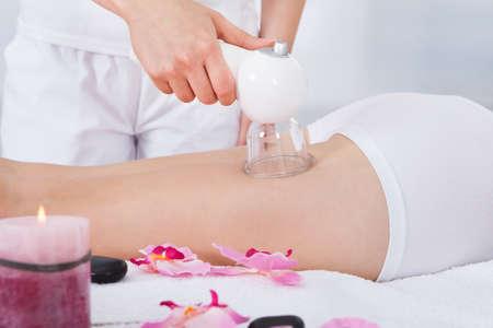 mujer celulitis: Primer plano de la pierna de la mujer recibiendo terapia láser in Spa
