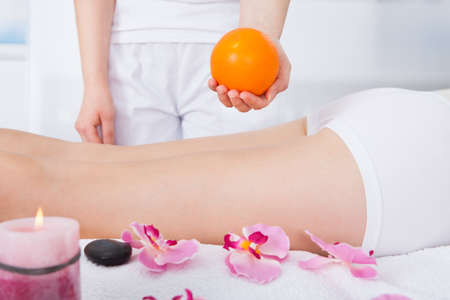 Female Massager Holding Orange Fruit In Front Of Woman Lying On Front photo