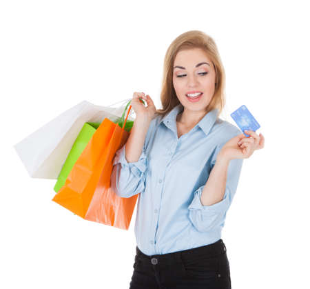 Smiling Woman With Shopping Bags Holding Credit Card Over White Background photo