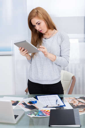 Portrait Of A Young Woman Using Digital Tablet In Office photo