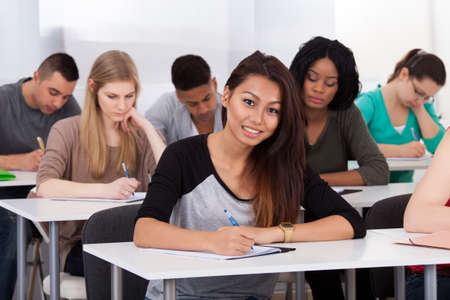 Portrait of smiling female college student sitting at desk with classmates in background