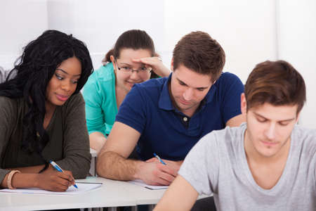 Female college students trying to cheat from male classmate during test in classroom photo