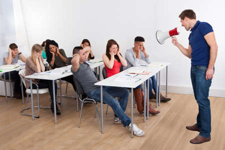 frustrated man: Angry teacher shouting through megaphone on university students in classroom