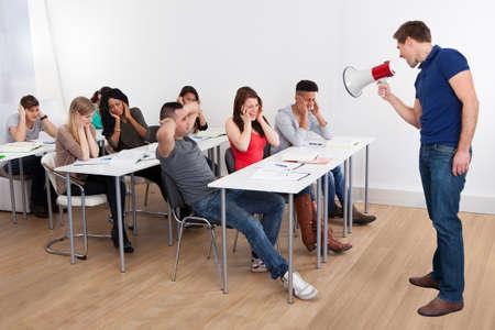 Wütend Lehrer durch Megaphon an Studenten im Klassenzimmer Standard-Bild