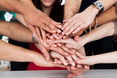 piling: Cropped image of university students piling hands at desk