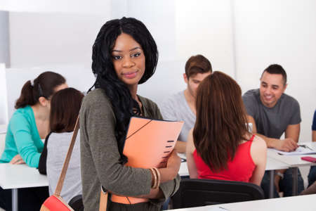Portrait of confident female college student holding file with classmates in background at classroom photo