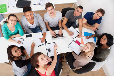 High angle view of university students doing group study at desk in classroom photo