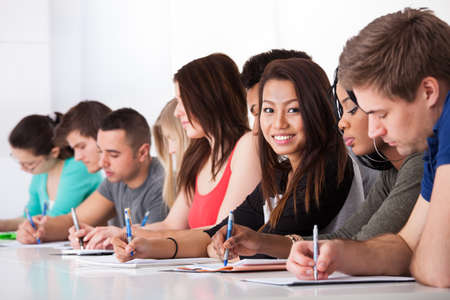 hispanic students: Portrait of smiling college student sitting with classmates writing at desk