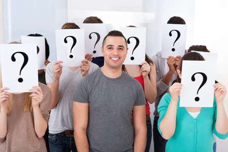 Portrait of confident college student surrounded by classmates holding question mark signs in classroom photo
