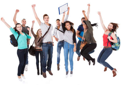 Full length portrait of successful university students with arms raised jumping over white background photo
