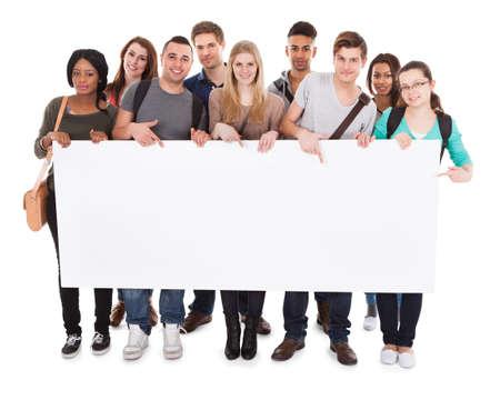 흰색 배경에 빈 빌보드를 표시 자신감을 다민족 대학 학생의 전체 길이 초상화 스톡 콘텐츠