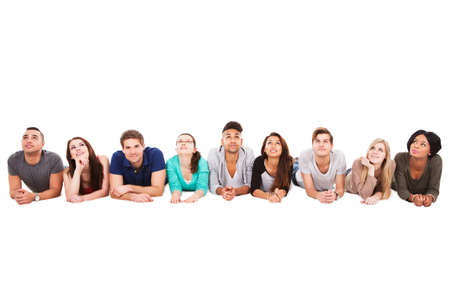 woman looking up: Portrait of confident multiethnic college students lying in a row over white background
