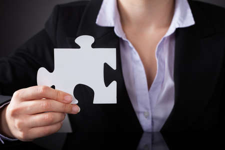 Close-up Of Business Person Holding White Puzzle photo