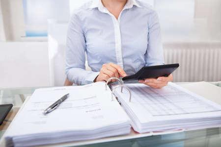 Primer Plano De Empresario Comprobación Una Factura En La Calculadora En El Escritorio