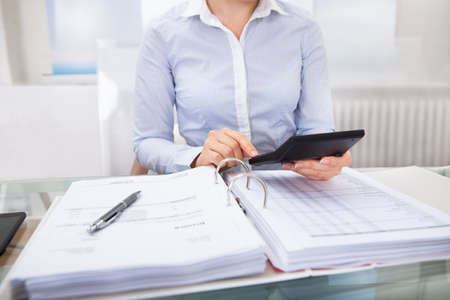 auditor�a: Primer Plano De Empresario Comprobaci�n Una Factura En La Calculadora En El Escritorio