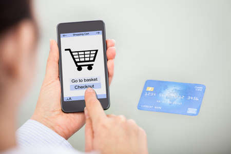 Close-up Of Businessperson Shopping Online With Mobile Phone And Credit Card photo