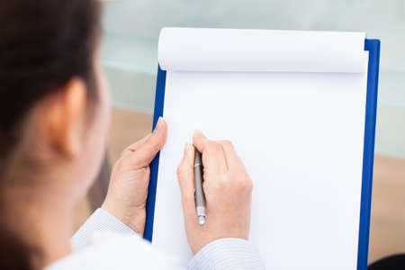 over the shoulder view: Close-up Of Businesswoman Writing With Pen  On Clipboard