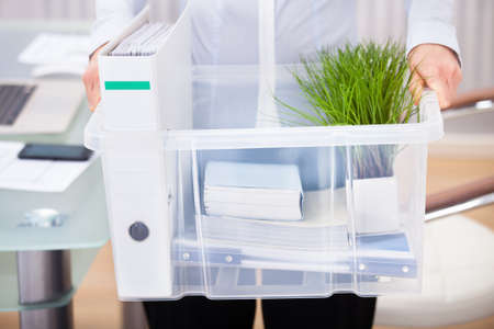 plastic box: Close-up Of Businessperson Carrying Office Supply In Plastic Container Stock Photo