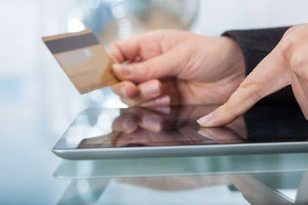 Cropped image of woman using credit card to shop online on digital tablet