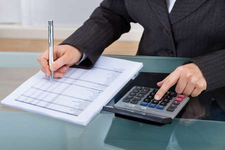 tax consultants: Midsection of businesswoman calculating tax at desk in office
