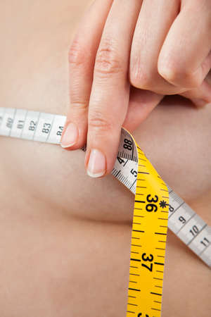 Closeup photo of woman measuring her breasts photo